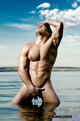 Chico guapo muy musculoso y sexy en el cielo y el fondo del mar