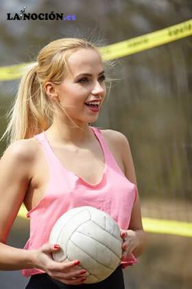 Alegre y atractiva chica rubia jugando al voleibol en la orilla del lago
