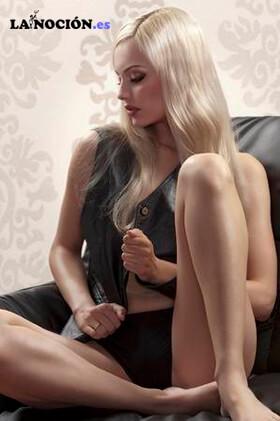 Rubia sentada en un sofá, vestida con un chaleco de cuero negro