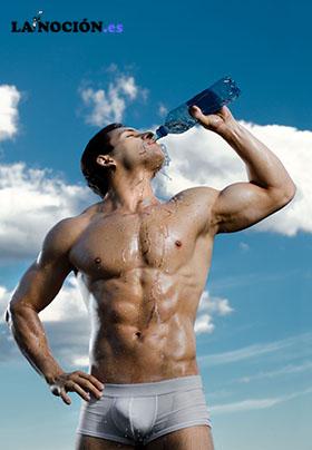Musculoso y guapo chico con fondo del cielo bebiendo agua