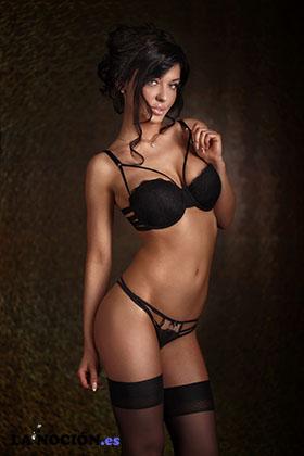 Elegante mujer morena sensual posando en ropa interior negra sexy, mirando a la cámara