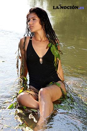 Guapa y atravtiva morena sentada en el agua