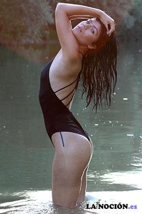 Joven y guapa morena lavandose el pelo en el agua