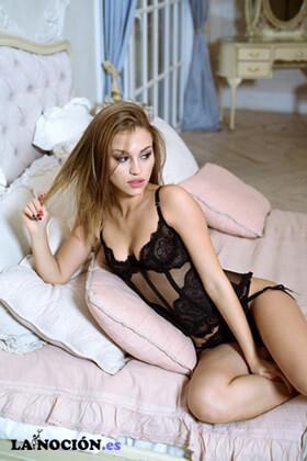 Hermosa dama sexy en bragas negras y sujetador tumbada en la cama