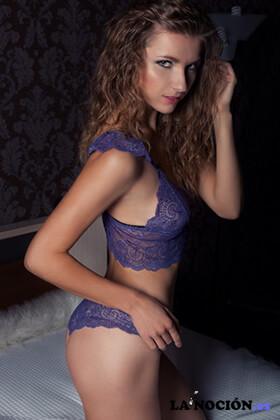 Hermosa joven y delgada atractiva en ropa interior de color púrpura en el dormitorio acostada en la cama en una habitación oscura