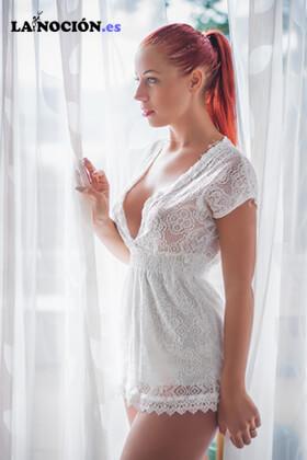 Hermosa mujer jóven de pie en el balcón con vestido de encaje blanco