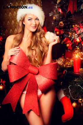 Hermosa mujer joven y sonriente en ropa interior celebrando la Navidad