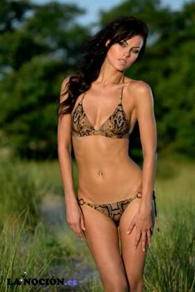 Modelo de moda morena posando en bikini durante la puesta del sol entre árboles