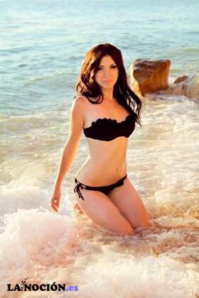 Mujer Morena sexy en bikini posando sobre las olas del mar en la playa