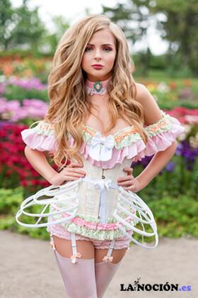 Mujer rubia sexy vestida con ropa interior de medias y corsé caminando en un jardín floreciente