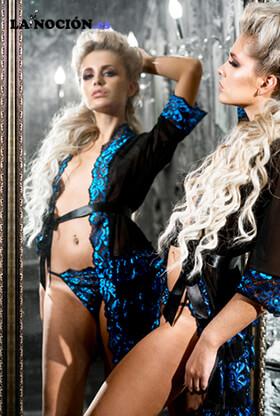Sexy mujer joven en bata de pie ante el espejo