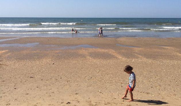 Un niño juega en la arena de una playa andaluza con paseantes y bañistas al fondo