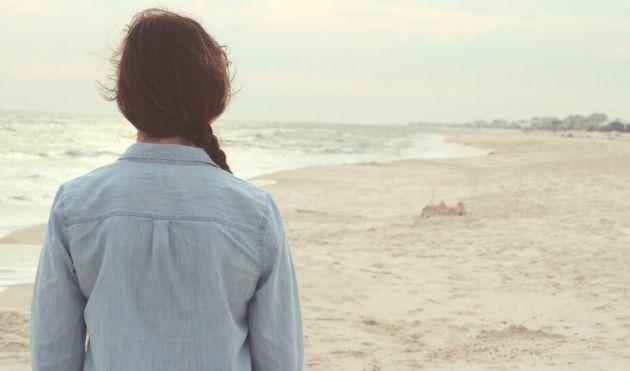 Una mujer joven camina por la playa