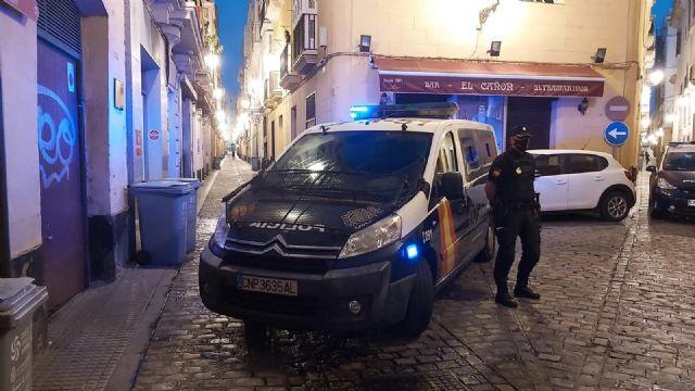 Un agente junto al coche de la Policía Nacional