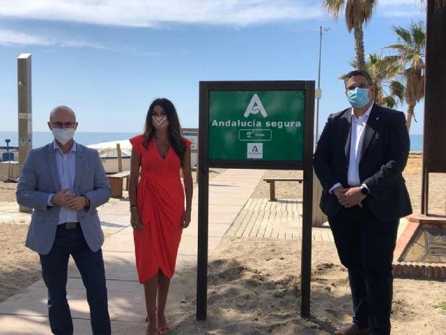 La delegada de Turismo, Nuria Rodriguez, junto al distintivo Andalucía Segura en una playa de Mijas, junto al alcalde, Josele González, a la derecha de la imagen