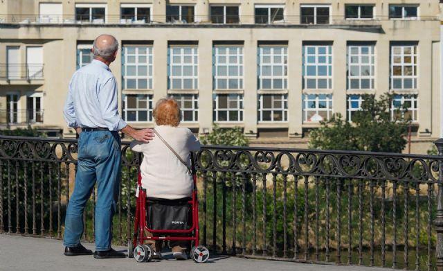 Personas mayor protegido con mascarilla pasea por el puente de Triana. - Eduardo Briones - Europa Press