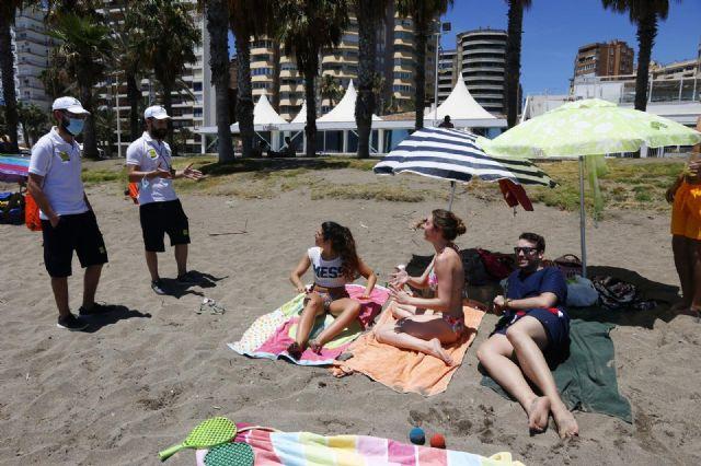 Una pareja de Vigilantes de la playa de Andalucía asesoran a bañistas sobre las medidas preventivas sobre el COVID-19 en la playa de La Malagueta