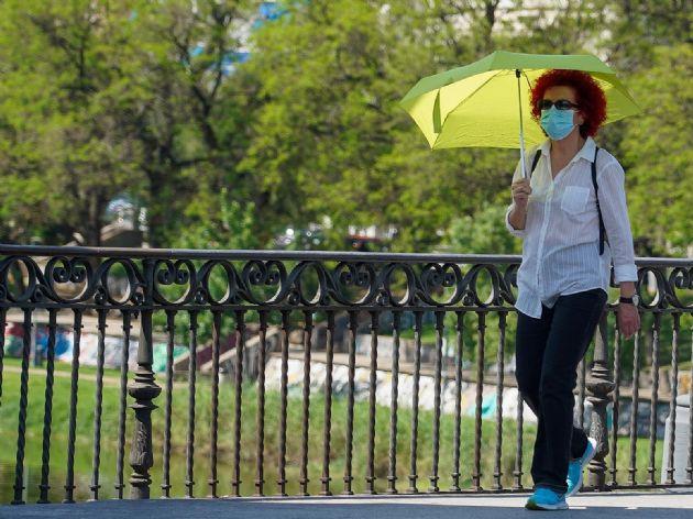 Mujer pasea con un paraguas amarillo por el puente de triana cuando el termómetro a alcanzado los 40 grados en el primer día de uso obligatorio de mascarillas en Sevilla a 21 de mayo del 2020 - Eduardo Briones - Europa Press