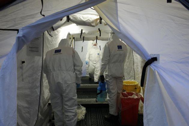 Trabajadores de proteccion civil se desinfectan contra el coronavirus en una carpa instalada en el hospital del PTS de Granada