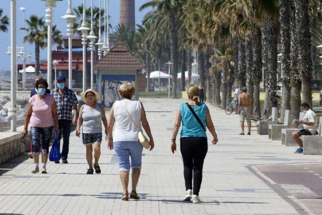 Paseantes disfrutan de la playa de Huelín durante la Fase 1 del Estado de Alarma