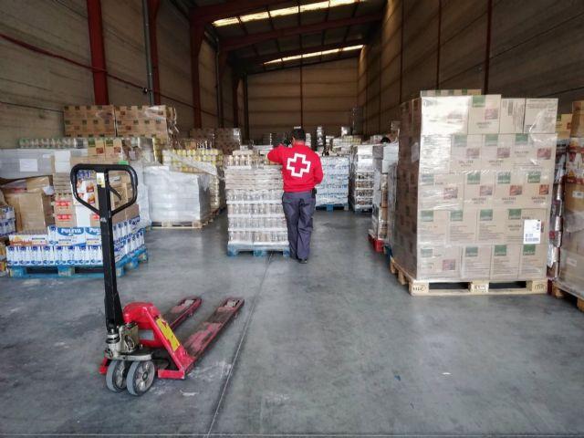 Un voluntario de Cruz Roja participa en el reparto de alimentos