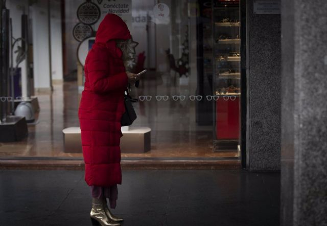Una mujer bajo un soportal espera que cese la lluvia