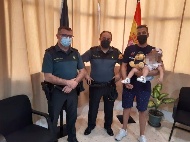 Agentes de la Guardia Civil, con la bebé auxiliada cuando se ahogaba en una piscina en Mairena del Alcor, Sevilla