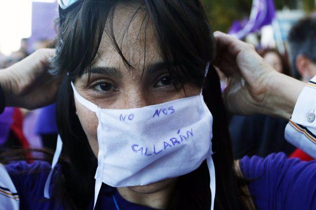 Una mujer se coloca una mascarilla en la que se lee No nos callarán durante la marcha por el Día Internacional de la Mujer en Málaga, (Andalucía, España), a 08 de marzo de 2020